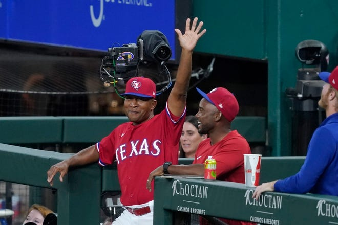 Texas Rangers third base coach Tony Beasley acknowledges cheers from fans during the second inning of the team's baseball game against the Oakland Athletics in Arlington on Friday. Fans cheered after an in-house announcement advising that Beasley would be throwing to Joey Gallo during the All-Star home run derby.