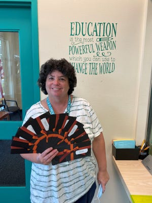 Tuttle Elementary teacher Amy Edelkind flashes gift cards provided by local foundations to celebrate summer school teachers and aides.