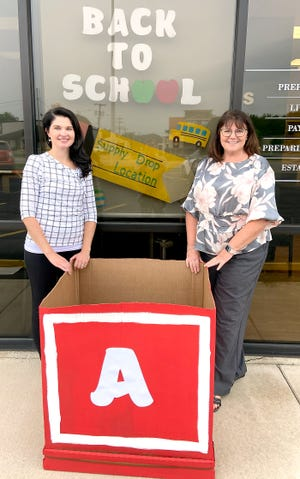 Kelli Besser and Norma Lohr show a donation bin atthe Edward Jones branch office at 68844 Broadus St., Sturgis, where a back-to-schoolsupplies drive is underway.