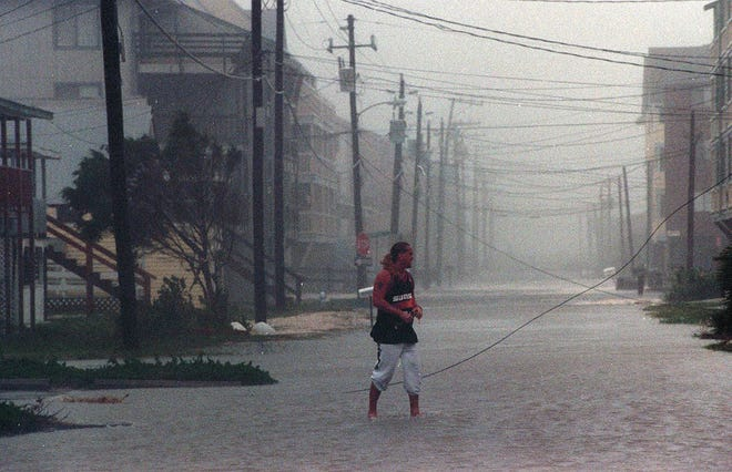 Mark Wagner crosses North Carolina Avenue in Carolina Beach during Hurricane Bertha. The storm came ashore between Wrightsville Beach and Topsail Island on July 12, 1996.