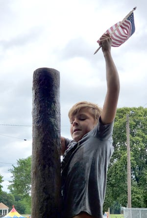 A participant in the Greasy Pole Contest conquers the pole and captures the flag.