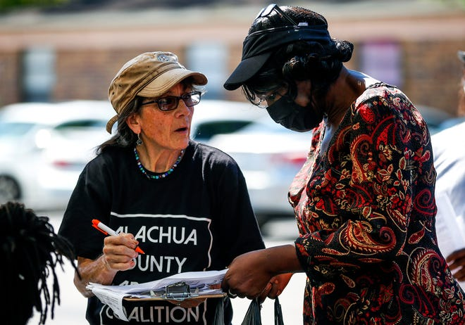 """Sheila Payne from the Alachua County Labor Coalition speaks with Renae McCoy during an event at Pine Ridge Apartments on July 10 in Gainesville, Fla. The Labor Coalition hosted the event after some residents received """"Notice to Vacate"""" mailers from the apartment management company."""