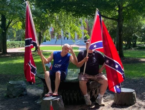 Two Alamance County men staged a protest on Saturday, July 10, 2021, at UNC-Chapel Hill's Unsung Founders Memorial. The men advocated white nationalism while carrying Confederate battle flags. One of the men can be seen here holding up a white power sign. [Photo from the UNC Anti-Racist Alerts Twitter feed]