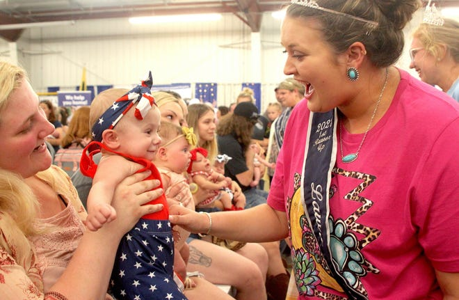 2021 Lawrence County Fair Queen first runner-up Addison Myers greets Rhylie Littrell during the Baby Contest held in the Expo Hall Monday. Littrell is held by her mother, Josie Sanders.