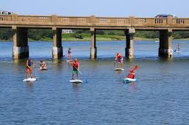 Stand-up paddleboarders and kayakers along the Bass River.