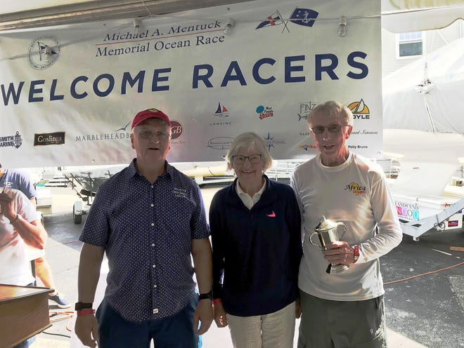 Overall winners Jud Smith and Bump Wilcox are shown receiving their trophy from Liz Mentuck, wife of the late Mike Mentuck for more than 50 years. Mike was the past commodore of the Boston Yacht Club.