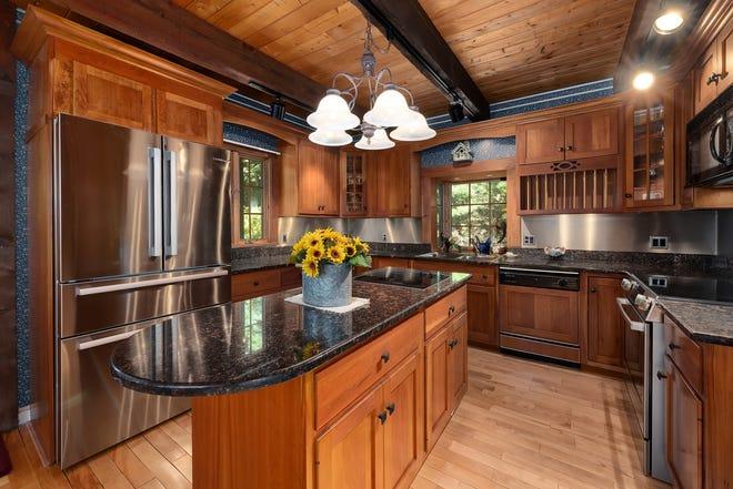 De U-vormige keuken heeft een houten dak met plafonds en een flinke houten kast, en een terugloopreling met roestvrijstalen inbouwapparatuur en granieten werkbladen.