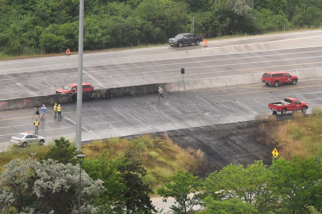 Workers assess the area Tuesday on northbound Interstate 75 near Big Beaver where a tanker truck crashed and caught fire on Monday in Troy on July 13, 2021.