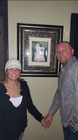 Belinda and her Husband standing in Front of a picture of her grandmother, Ellen