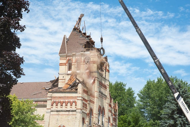 A weight held by a crane is used to smash the bell tower of the old Holy Trinity Church on Monday.