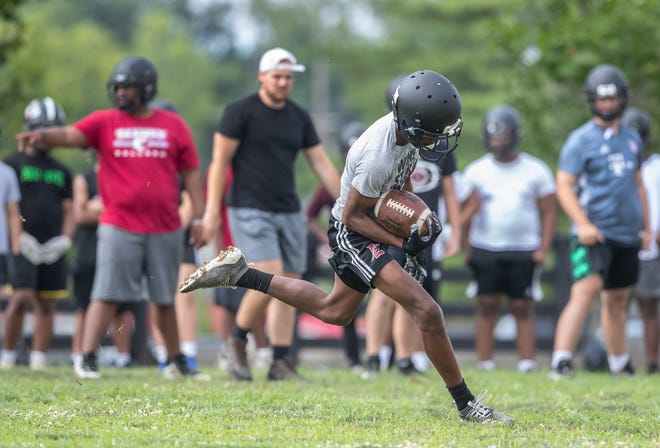 A receiver hauls in a pass during the first football practice of the year at Ballard High School. July 13, 2021