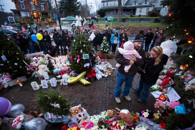 A family embraces while visiting a memorial to the victims of the recent school shooting in Sandy Hook Village in Newtown, Connecticut, December 16, 2012. REUTERS/Lucas Jackson