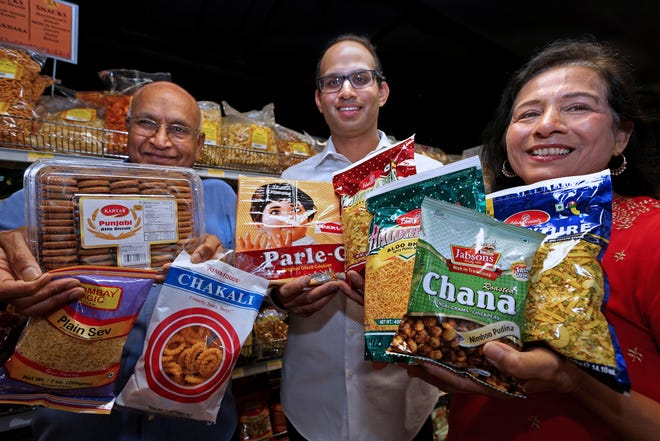 The Sanghavi family from left, Dinesh, his son Neil and wife Bharti, display snacks to consider while watching the Olympics. They're shown at their store, Indian Groceries & Spices at 10701 W. North Ave. in Wauwatosa, on July 9.