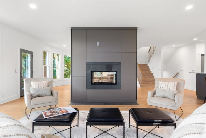 """This fireplace is an example of using the """"broken living"""" trend to break up large open spaces without using walls. This fireplace, made of acrylic imported from Austria, gently separates the living and dining areas in this Brentwood Hills home. Fireplace design by Nashville Modern Cabinetry. Staging by FP Staging."""