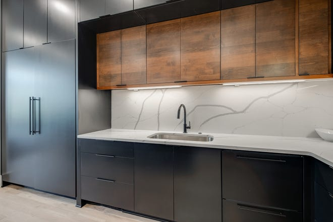 This Sylvan Park kitchen shows the beauty of adding wood cabinetry with another color. This homeowner chose black cabinetry with sleek, tone-on-tone hardware offset with a white marble countertop and backsplash that are the same material, which adds a seamless transition from the countertop to the wall.