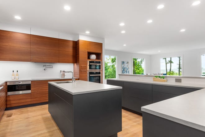 This kitchen designed by Nashville Modern Cabinetry shows how different colors and textures can add interest to a kitchen. Also notice the cabinetry doesn't have hardware. This touch-to-open technology is not only functional but creates a seamless look in a kitchen by allowing the wood grain to flow across cabinets without being broken up by cabinet door spacing or hardware. Staging by FP Staging.