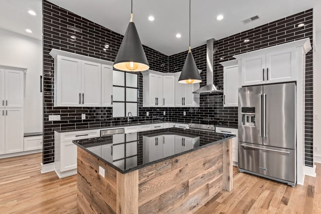 This secondary kitchen in an Oak Hills home in Nashville shows how a wood-grained island can not only anchor an open kitchen, but also add interest and depth to white cabinetry. The black tile wall adds drama while allowing the white cabinetry to pop. The black island top adds a cohesive element to the room, tying it all together.