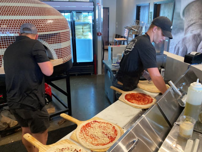 Beryl Walters (right) makes pizza during lunch hour at the new Pataskala Elliot's location on July 13.