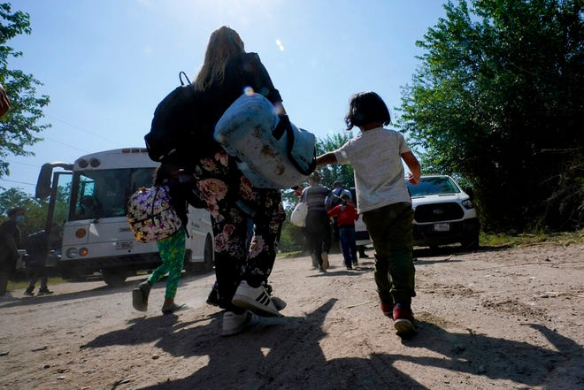 In this June 16, 2021, file photo, a migrant family from Venezuela move to a Border Patrol transport vehicle after they and other migrants crossed the U.S.-Mexico border and turned themselves in Del Rio, Texas. A Justice Department attorney says the U.S. Centers for Disease Control and Prevention will issue an order this week about treatment of children under a public health order that has prevented migrants from seeking asylum at U.S. borders.
