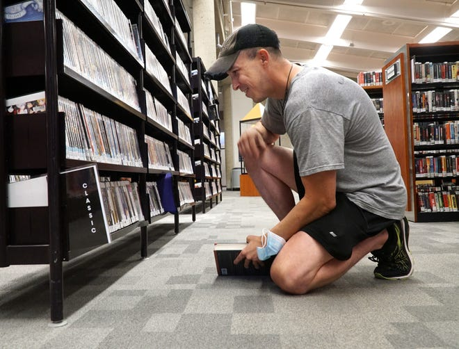 Brian Webber checks out some potentials in the DVD section of the Farmington Community Library at 32737 W. Twelve Mile Road in Farmington Hills on July 13, 2021.