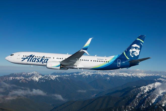 An Alaska Airlines jet flies over a mountain range.