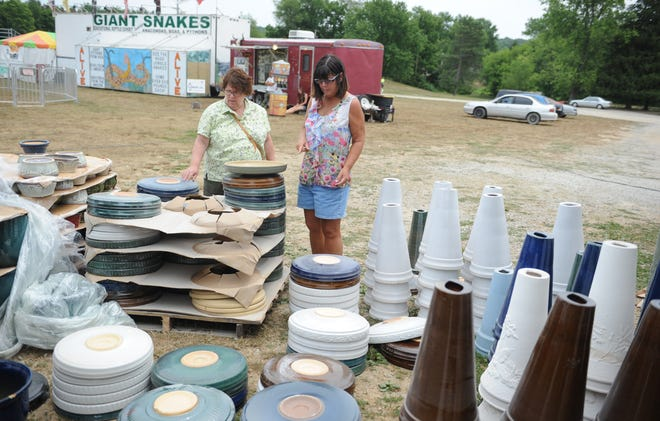 From left, Judie Snyder and Cathy Melton look over pottery at the Roseville Progress Club booth at Village Park in Crooksville at the 2012 Pottery Festival. Traditional pottery vendors and exhibitor activities are on the schedule this year, but festival organizers are bringing back some old school activities from decades ago.