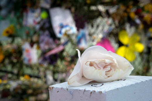 A rose wilts at the memorial wall near the Champlain Towers South site on Tuesday, July 13, 2021.