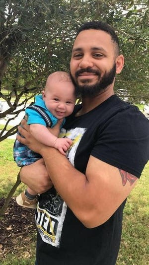 Cameron Wilcox, shown holding son Phoenix Wilcox, was a loving father, his parents say.