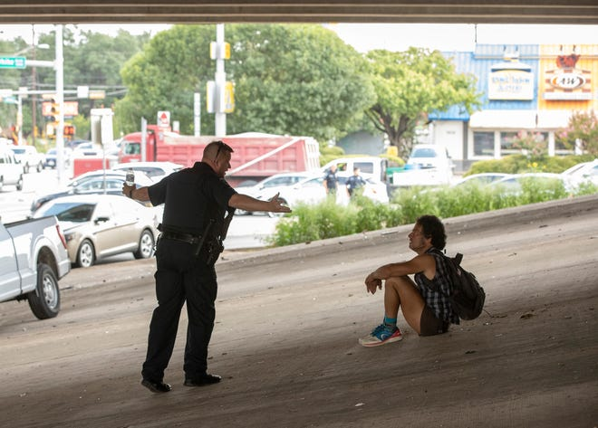 Austin police officer J. Binder talks to Rudy, who has been homeless for four years and who was watching as Austin Resource Recovery workers removed a homeless camp under the U.S. 290/Texas 71 overpass at Menchaca Road on July 14. [AMERICAN-STATESMAN]