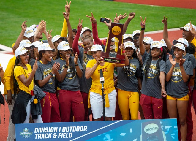 Southern Californoa's Caryl Smith Gilbert, center, holds the trophy after USC won the title at the NCAA Outdoor Track and Field Championship in Eugene, Oregon.  Eug 061212 Ncaa 14