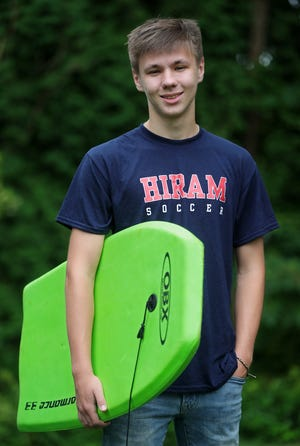 Travis Shrout of Stow holds the bodyboard he used to rescue a woman and her son from drowning in a riptide while on vacation in North Carolina.