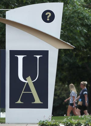 People walk near Buchtel Commons during a July 14 tour of the University of Akron campus.