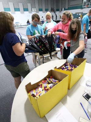 Volunteers at a Marlington Local Schools table help a parent load up a backpack with supplies during a school supply giveaway in August 2020 at Alliance Friends Church. Events such as this currently are being planned for 2021.