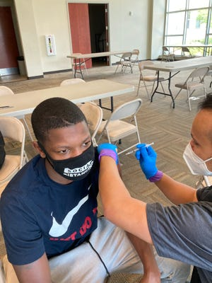 Ricco Wright, 17, gets his second COVID-19 shot from EMT Rico Weiland at a mobile clinic Wednesday at the Augusta Municipal Building hosted by the East Central Health District.