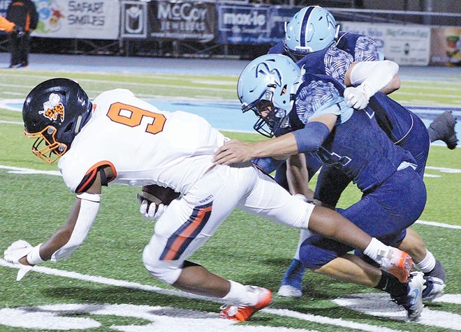 Bartlesville High defensive players, right, take down an opposing player during tight action last season.
