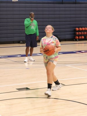 SRC Head Coach Marc Lowe looks on as a participant in an earlier basketball camp goes in for a shot. An additional camp is scheduled for August 8 at the Canton Campus.