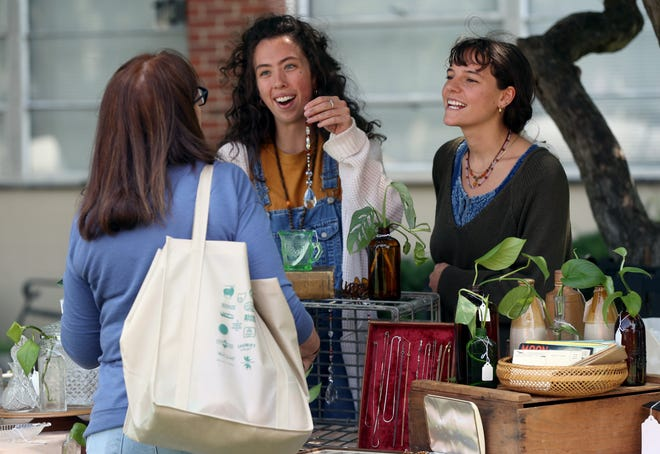 Megan Grubb (right) and Olivia Slater (center), both of Lancaster, help Jenny Held of German Village make selections at their vendor booth July 3 at the St. Mary Farmers Market in German Village.