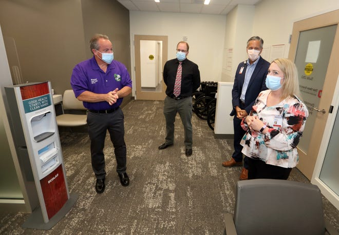 Kendra Long, practice manager of the Ohio State University Wexner Medical Center's Outpatient Care Pickerington office, describes the lobby to Pickerington Mayor Lee Gray (left), Pickerington economic-development director Dave Gulden and Garth Dahdah, the center's director of strategic growth and facilities operations for ambulatory services, during a tour of the facility, 1025 Refugee Road, on July 13.