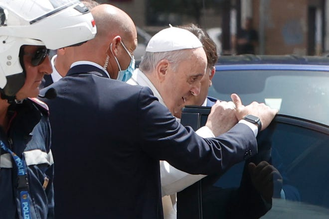 Pope Francis stops to greet police that escorted him as he arrives at the Vatican on Wednesday, July 14, 2021, from a Rome hospital where he had spent 10 days after undergoing surgery to remove half his colon.