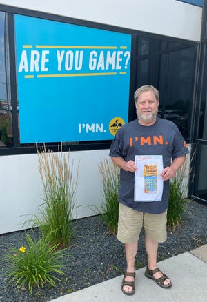 Wearing his new Minnesota Lottery t-shirt, Kim Christopherson displays a copy of his $200,000 winning 'Red-Hot Riches' scratch-off ticket at Minnesota Lottery headquarters in Roseville.