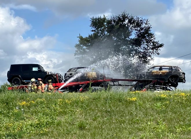 Firefighters extinguish flames that destroyed nine Mercedes vehicles and a trailer hauling them after it caught on fire while traveling west on Interstate 70 Tuesday. The fire closed I-70 for approximately two hours, but no injuries were reported.