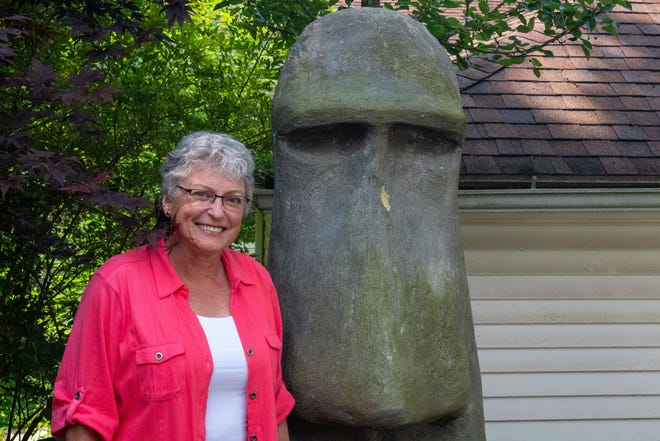 Lizbeth Mang stands next to her moai-inspired garden statue. It was surrounded by the poisonous English ivy until she removed the plant nearly two weeks ago. Her run-in with the ivy sent her to two different physicians.