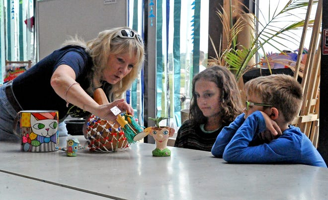 Melody Kirby (left), art teacher at Wooster Christian School, shows Violet Fridley (center) and Zac Schar (right) examples of artwork they will be creating at this year's summer art camp. Fridley and Schar participated in last year's program and said they are looking forward to coming back this year.