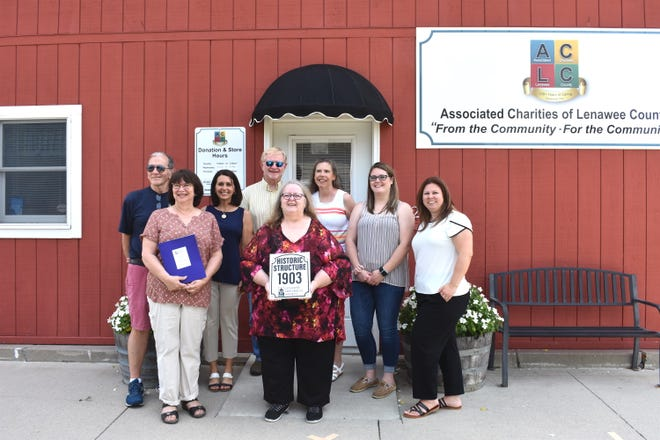 Board members of Associated Charities of Lenawee County and executive director Delight Creech, holding plaque, and state Rep, Bronna Kahle, R-Adrian, third from left, pose for a photo last week in front of 221 S. Tecumseh St., Adrian, the location of Associated Charities. The South Tecumseh Street address was recognized as a historic structure by the Lenawee Historical Society.