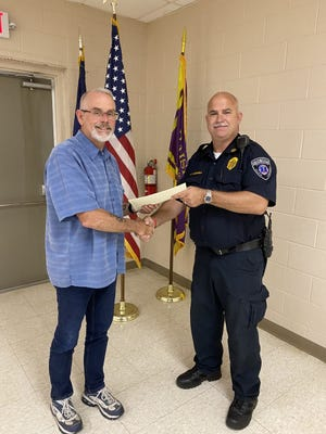 Raisin Township Supervisor Tom Hawkins presents fire chief Jim Hannah with a certificate of appreciation during the township board's meeting Monday.
