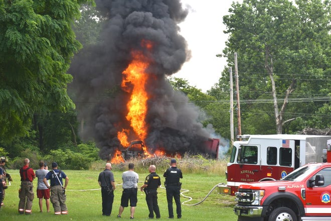 A Lenawee County Drain Commission dump truck was fully engulfed in flames just after 11 a.m. Wednesday in Adrian, near the intersection of West Maple and Springbrook Avenue, after the truck caught some overhead power lines while dumping brush into a compost pile. The driver of the truck was unharmed and made it away from the scene safely.