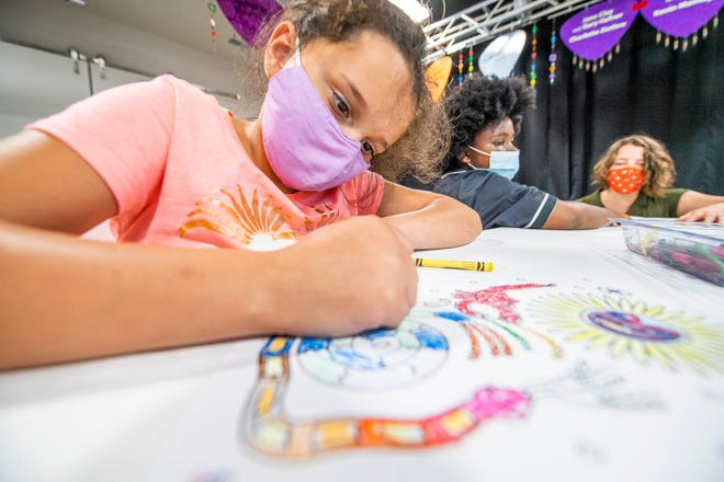 Dassi Waltheo, left, wears a face mask while working on a crayon coloring inspired by huichol yarn paintings July 13 during a Lotus Education and Arts Foundation workshop. Monroe County health officials are urging people everyone to wear masks during indoor activities.