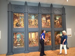 """Security staff and educator Rebecca Hinton chats with docent Kathie Durkel in front of Felipe Vigarny's (sometimes called Bigarny), """"Scenes from the Life of the Virgin."""" Relief, wood with gold."""
