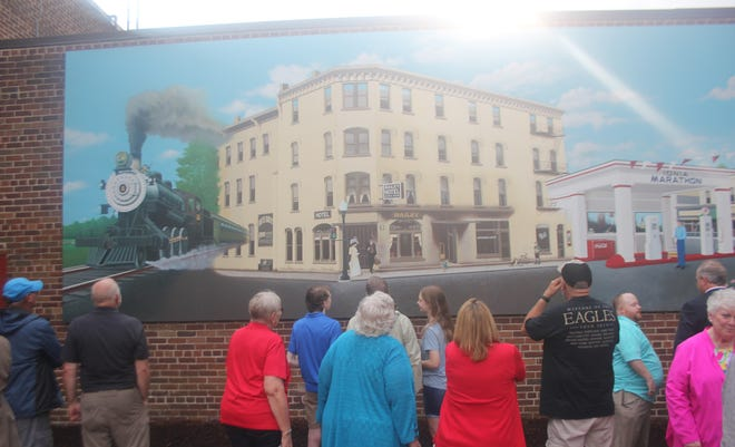 Members of the public view the Ionia mural project following its dedication ceremony Tuesday, July 13, outside of the Ionia Theatre, 205 W. Main St., in downtown Ionia.