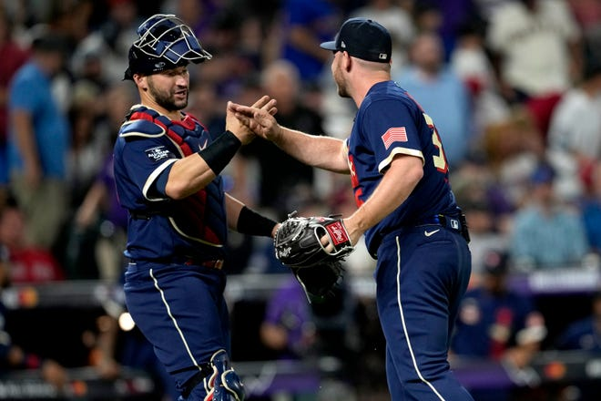 American League's Liam Hendriks, of the Chicago White Sox, right, greets catcher Marcus Semien, of the Toronto Blue Jays, after the MLB All-Star game Tuesday in Denver. The American League defeated the National League 5-2.